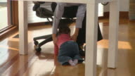 MS TU Young woman with baby girl (6-11months) on laps talking on phone in home office / Richmond, Virginia, USA