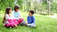 Giovane donna con bambini discutendo in green park.