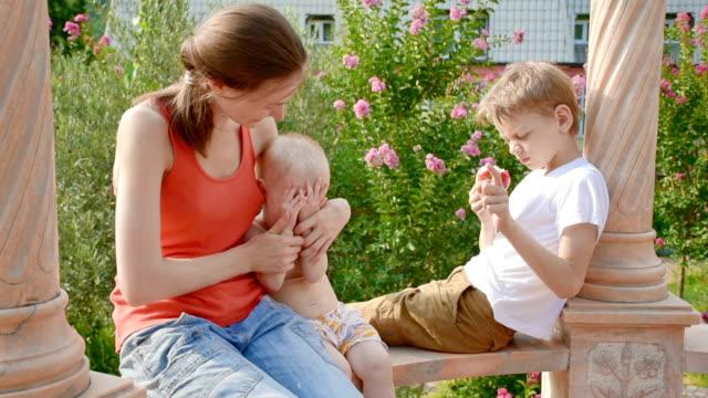 Jonge vrouw met kinderen in de zomer gazebo