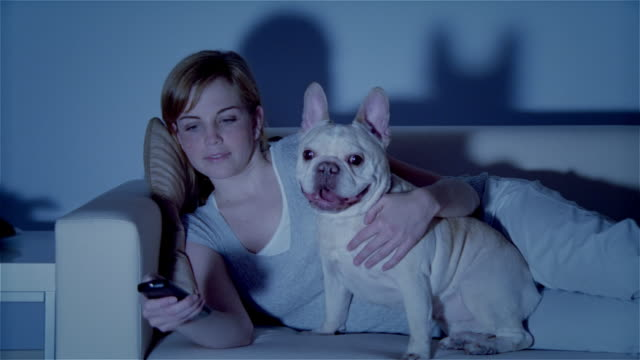 MS, Young woman with dog lying on sofa, watching TV