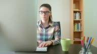 Young woman  with eyeglasses in front of the computer.