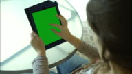 Young woman with green screen tablet