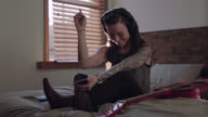 WS SLO MO. Young woman with headphones dances to music in bed.
