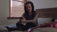 WS SLO MO. Young woman with headphones sings along to music from smartphone in bed.