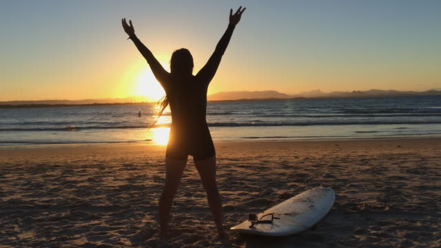 A young woman with her arms up, feeling the wind and the sun, in a beautiful sunset at Byron Main Beach