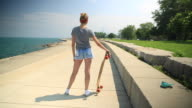 A young woman with her longboard skateboard.