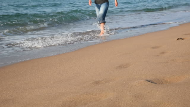 Young Woman With Jeans Walking From The Beach