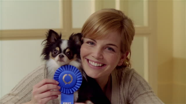 CU, Young woman with long coat Chihuahua holding first place rosette, portrait