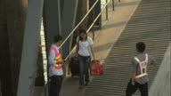 WS HA TD Young woman with luggage walking down ramp to board ferry, Yuhuan County, Zhejiang, China