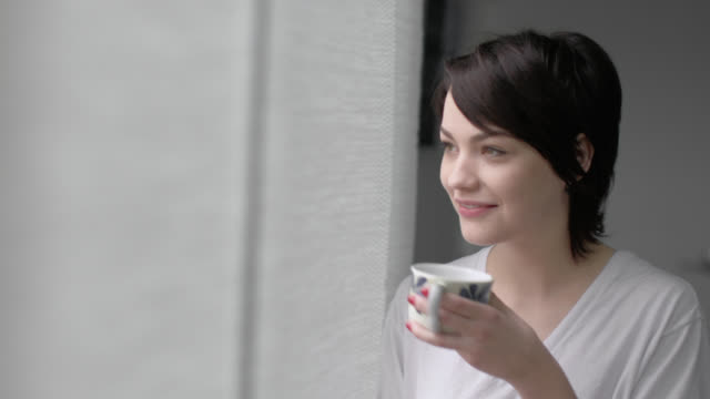 Young woman with morning coffee walks to window and looks out, turns to look back at bed