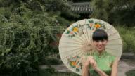 WS PAN Young woman with paper umbrella walking across courtyard / Beijing, China
