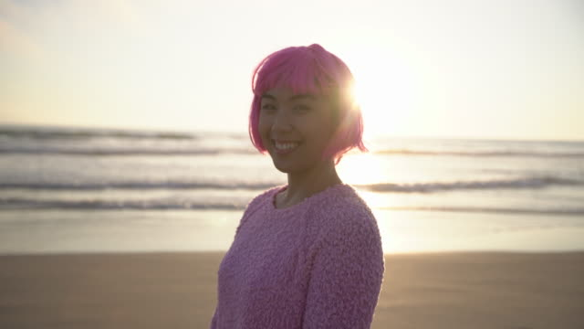 MS Young woman with pink hair smiling on the beach