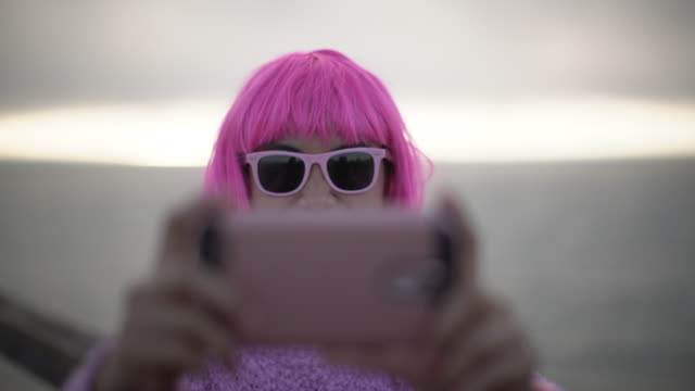 CU Young woman with pink hair taking a selfie