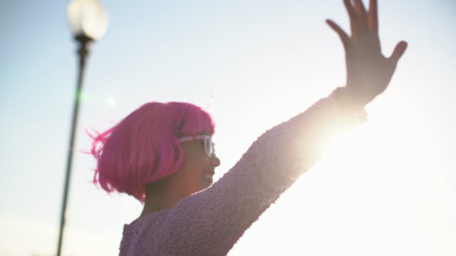 MS young woman with pink hair waving her arms in the sunlight