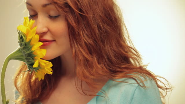 CU TU Young Woman with Red Hair Smelling Sunflower