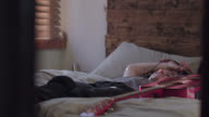 WS SLO MO. Young woman with smartphone listens to music in bed and grooves to the beat.
