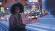 Young woman with smartphone smiles and laughs at camera on Las Vegas street corner.