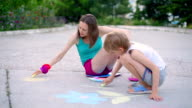 young woman with son draws a chalk on asphalt