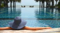 Young woman with straw hat on the pool