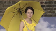 Young woman with umbrella, camera zooms out and she spins umbrella