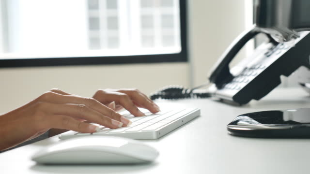 A young woman working at a desk with a computer keyboard.