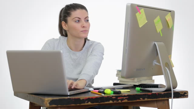 Young woman working in front of the PC and laptop in the same time .