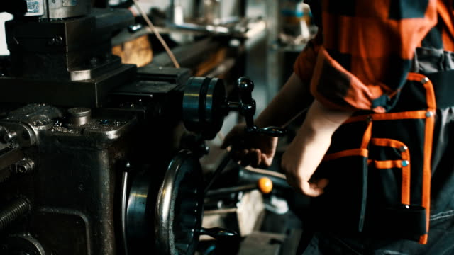 Young woman working on lathe machine in a workshop