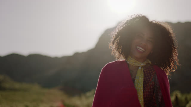 MED SLO MO. Young woman wrapped in red shawl looks at the camera and laughs in the Nevada desert.