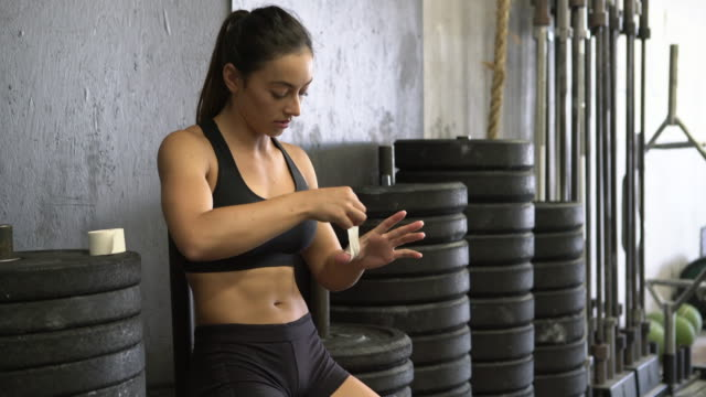 MS Young woman wrapping her hand before working out.