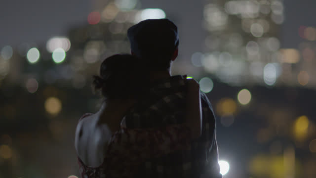 Young woman wraps her arms around her boyfriend as they look out on a city skyline