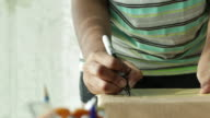 ZO CU Young woman writing address on package and putting pen back in pot.