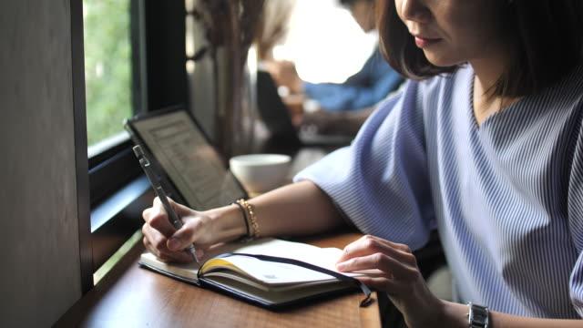 Junge Frau in ihrem Tagebuch im Café Tagebuch zu schreiben
