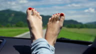 Young woman's feet with polished nails on a dashboard
