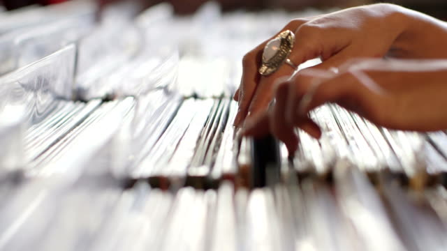CU A Young Woman's fingers flick through a rack of vintage records