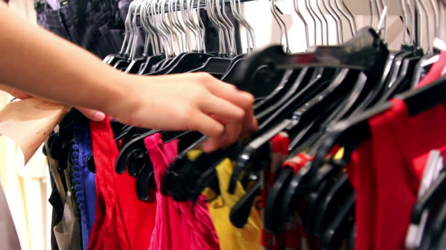 Young Woman's Hands as she Shops for Dresses