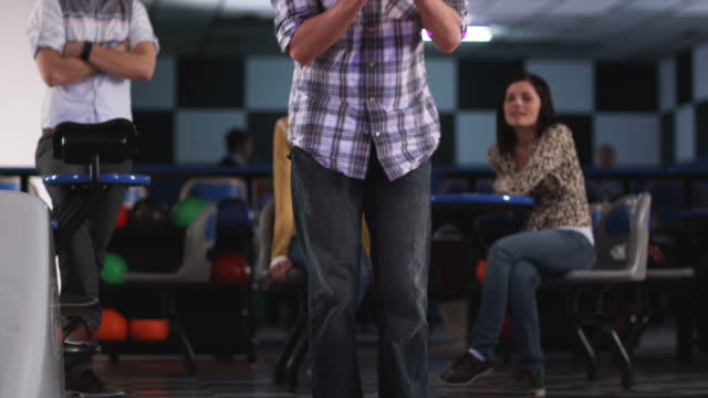 young women at a bowling alley watching a young man bowl and looking at his butt