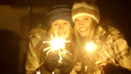 Young women burning sparkler during winter
