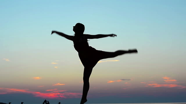 HD: Young women dancing classic ballet against the sunset