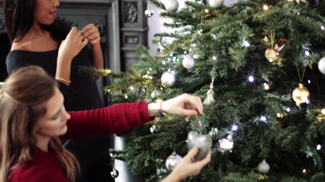 Young women decorating Christmas tree with Christmas ornaments