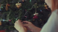 Young Women Decorating Christmas Tree With Ornaments
