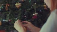 Jonge vrouwen versieren kerstboom met versieringen