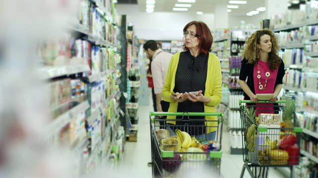 Young women helping senior women to use tablet for shopping in supermarket