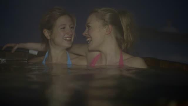 Young women in bikini enjoying steam water in hot tub during winter