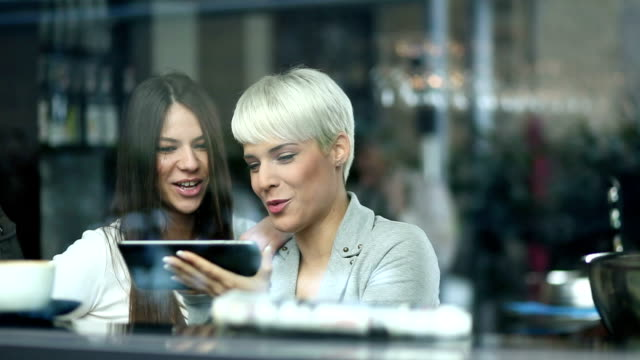 Young women in cafe using tablet
