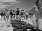 B/W 1951 young women in swim suits taking turns running through tire course on beach / Florida