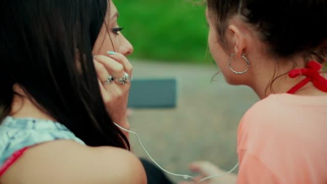 Jonge vrouwen luisteren van muziek met een mobiele telefoon buiten
