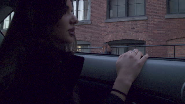 Young women looking out of car window, sunset NYC
