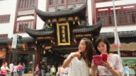 Young women reading guidebook in Yuyuan Tourist Mart