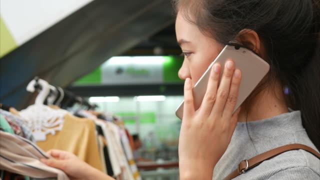 unga kvinnor shopping på gatan marknaden och använda telefon