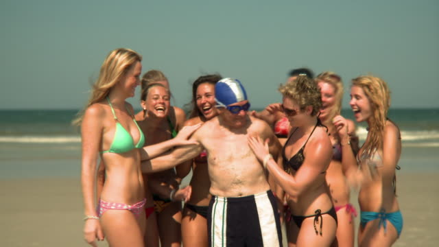 MS Young women surrounding and embracing elderly man standing on beach, Jacksonville, Florida, USA